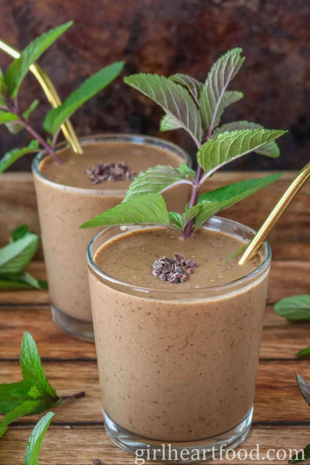Two glasses of chocolate mint smoothie, one in front and one behind.