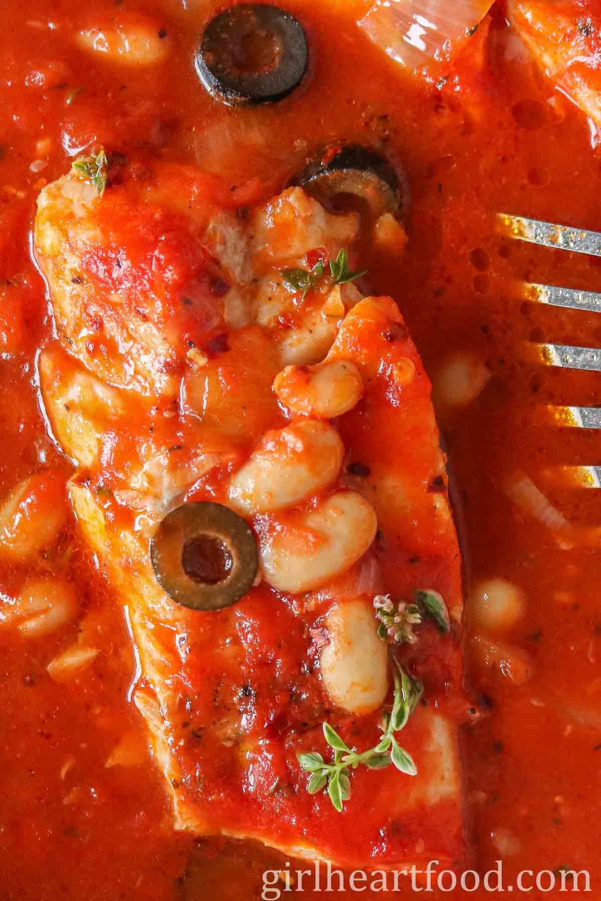 Close up of a cod fillet in tomato sauce with olives and beans and fresh thyme on top.