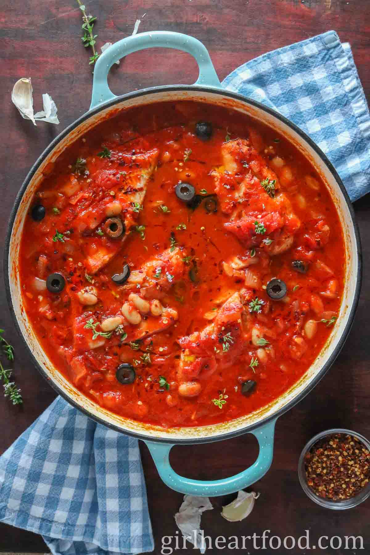 Large round blue dish with cod fillets in spicy tomato sauce with olives and beans.