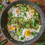 Skillet of eggs in salsa verde garnished with fresh herbs and sliced jalapeno.