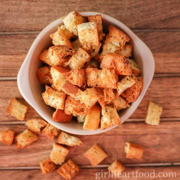 Overhead shot of a bowl of homemade croutons spilling out.
