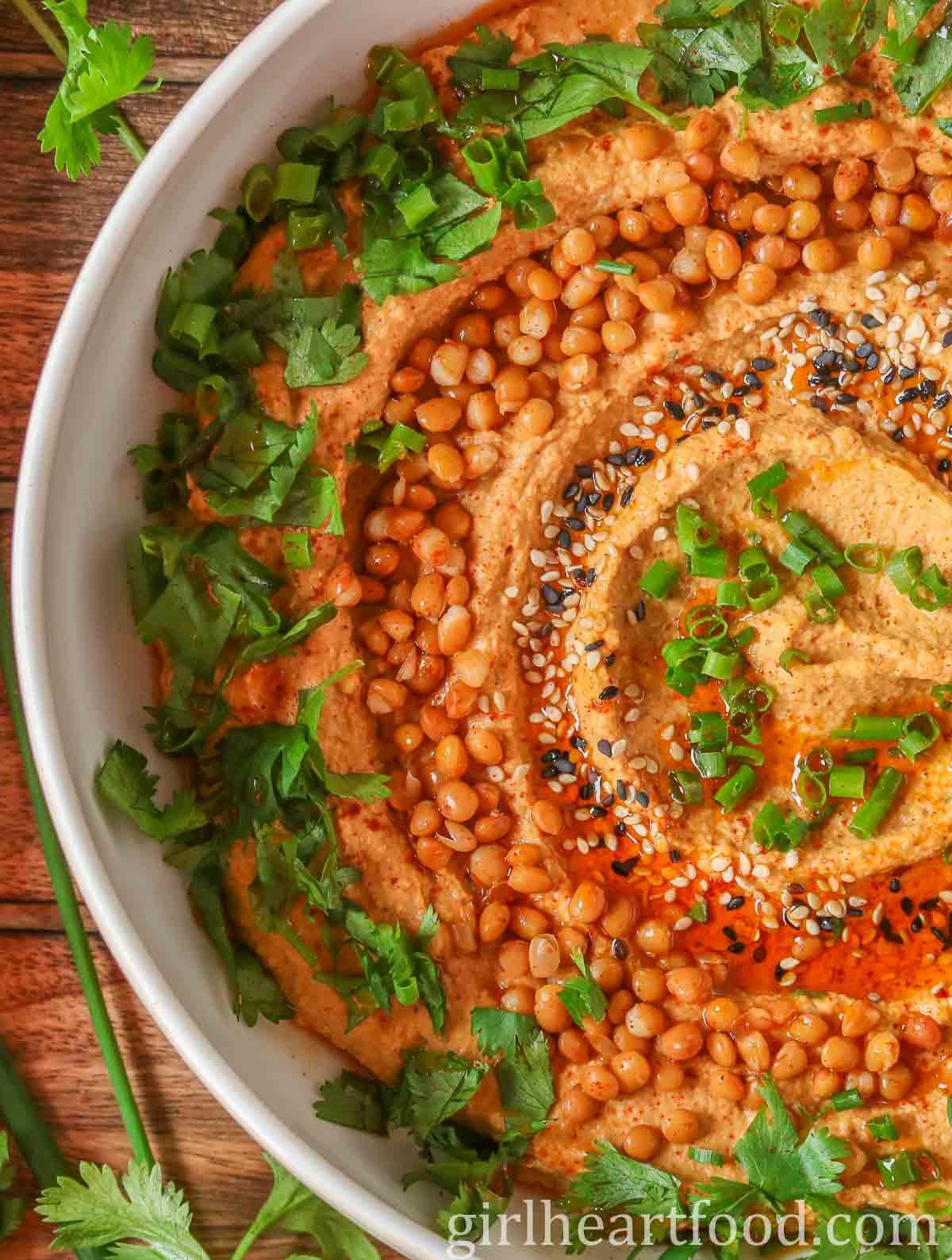Close-up of the left-hand side of a bowl of garnished lentil hummus.