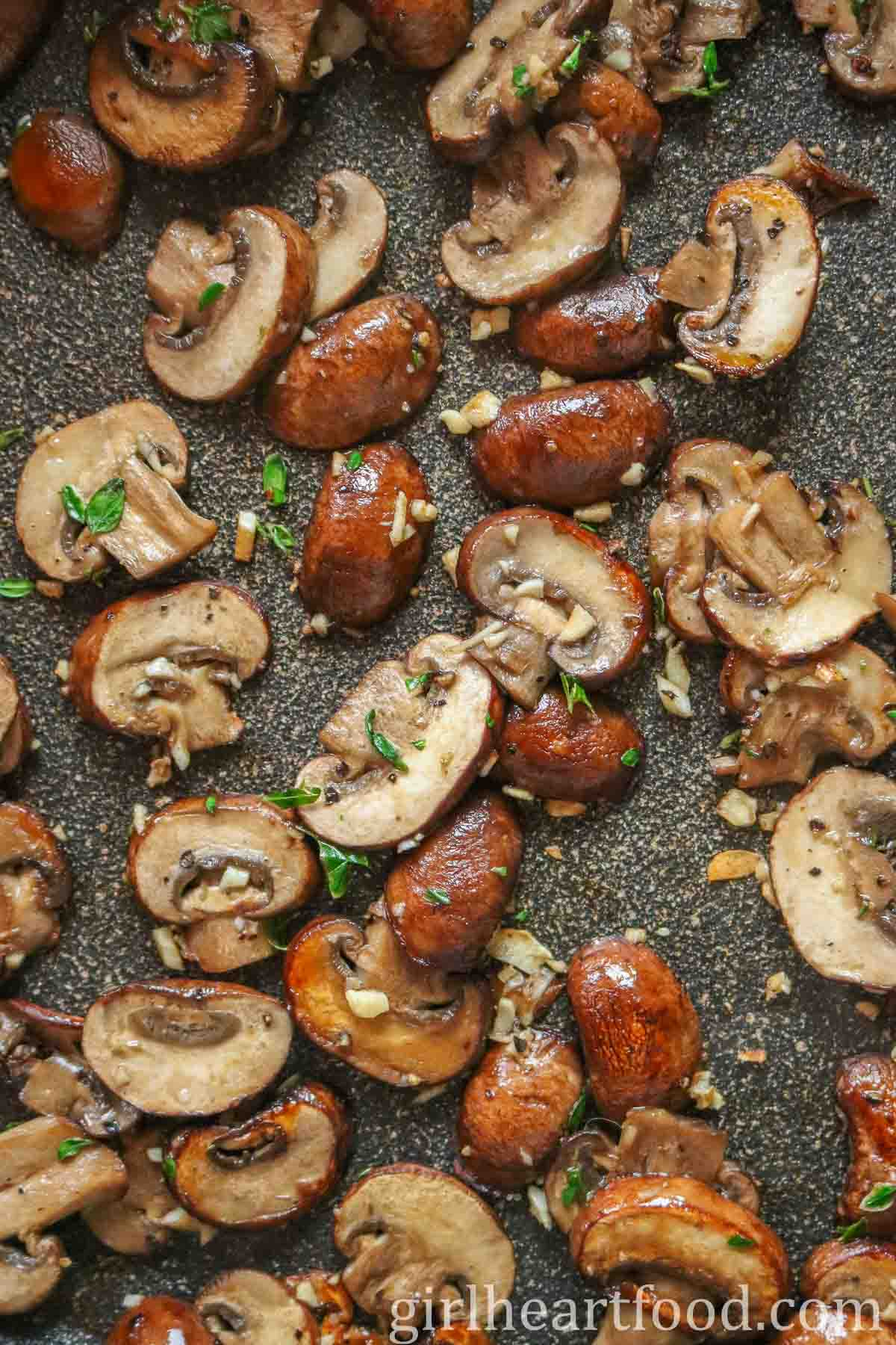 Slices of sautéed mushrooms with garlic and thyme in a non-stick pan.