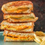 Tall stack of dill pickle grilled cheese sandwiches next to chips.