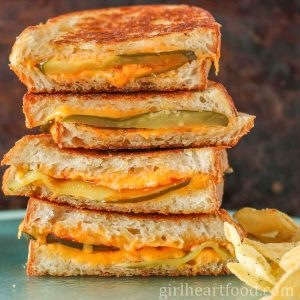 Stack of dill pickle grilled cheese sandwiches next to potato chips.