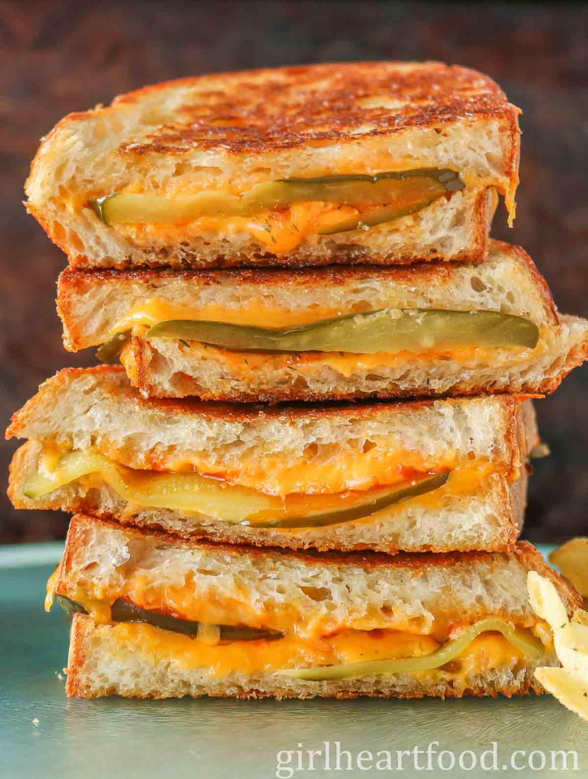 Tall stack of pickle grilled cheese sandwiches.
