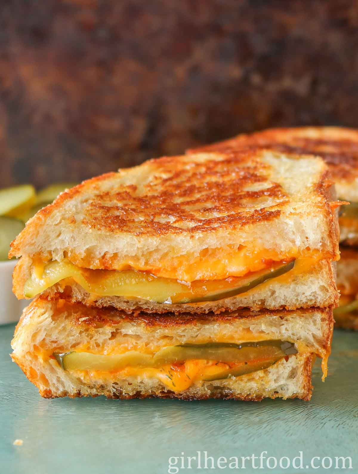 Close up of two halves of a pickle cheddar grilled cheese sandwich stacked on top of each other.