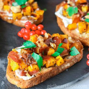 Roasted acorn squash crostini with prosciutto, goat cheese and parsley on a platter.