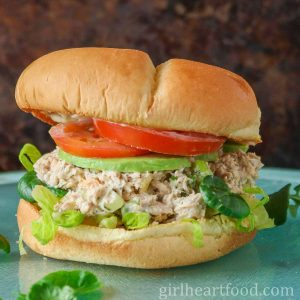 Salmon salad sandwich with veggies and avocado.