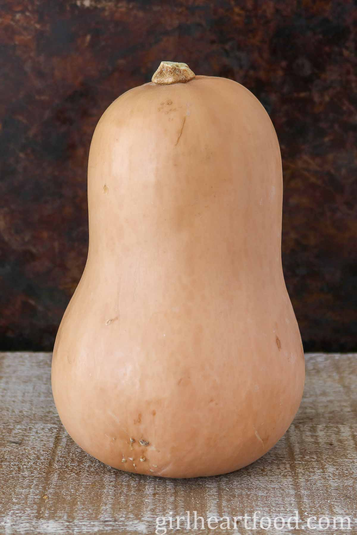 Close up of a whole butternut squash on a wooden board.