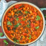 Overhead shot of a large round pot of butternut squash chickpea curry garnished with fresh cilantro.