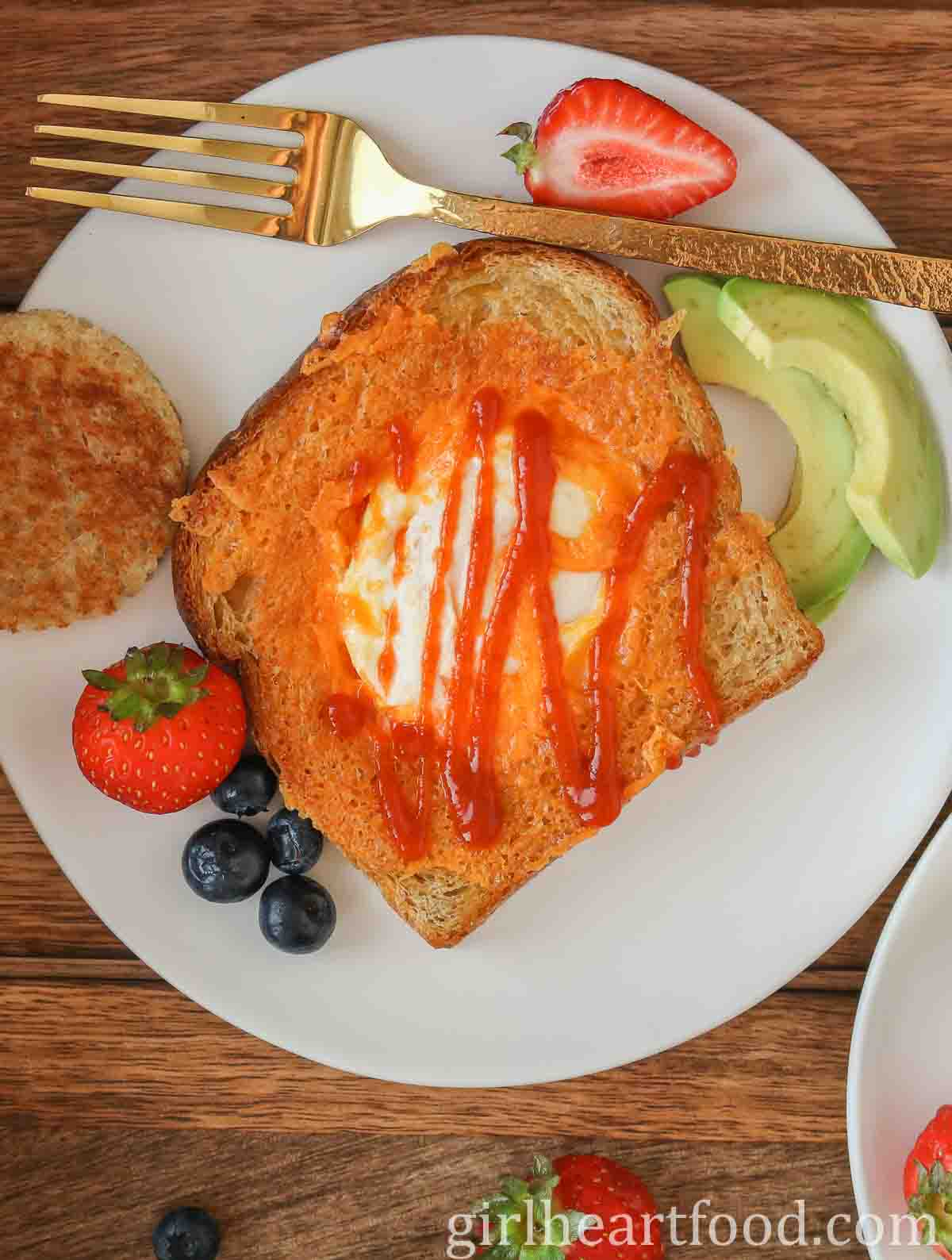 Slice of cheesy egg toast drizzled with hot sauce, next to sliced avocado, berries and a gold fork.