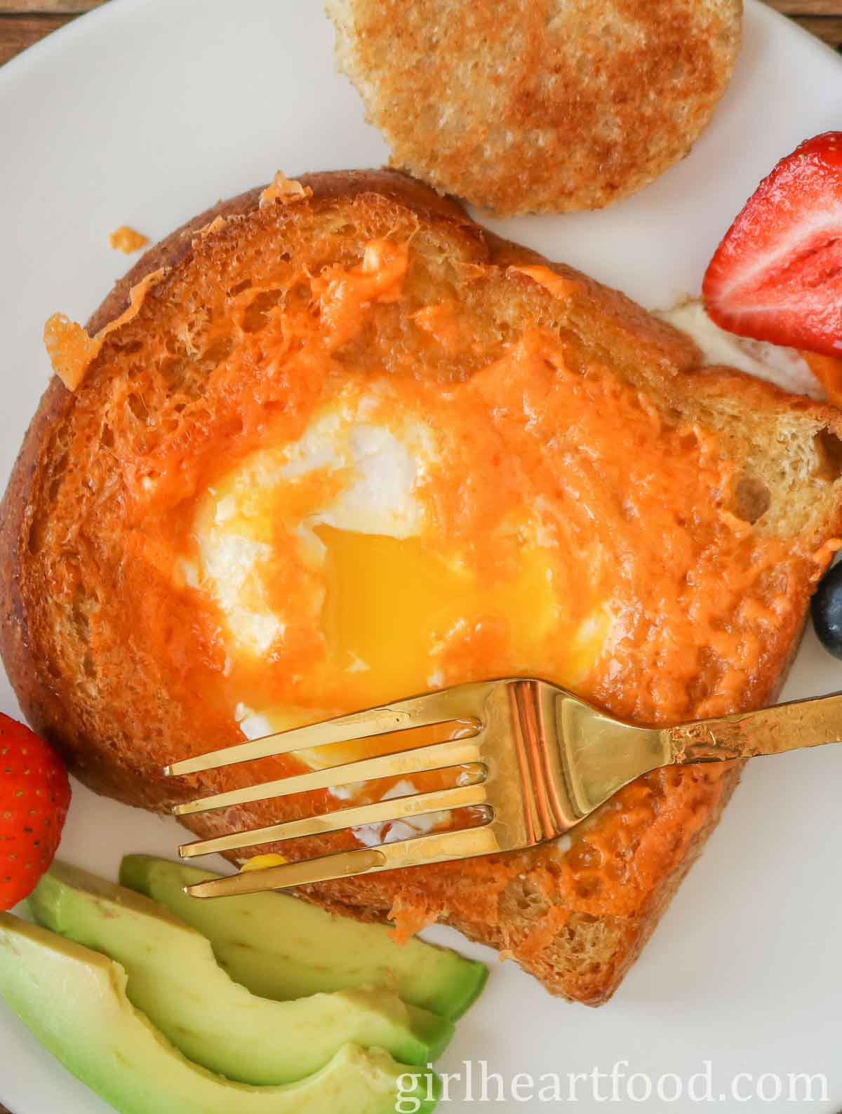 Egg-in-a-hole toast (with the yolk broke) and a gold fork resting on top of it.