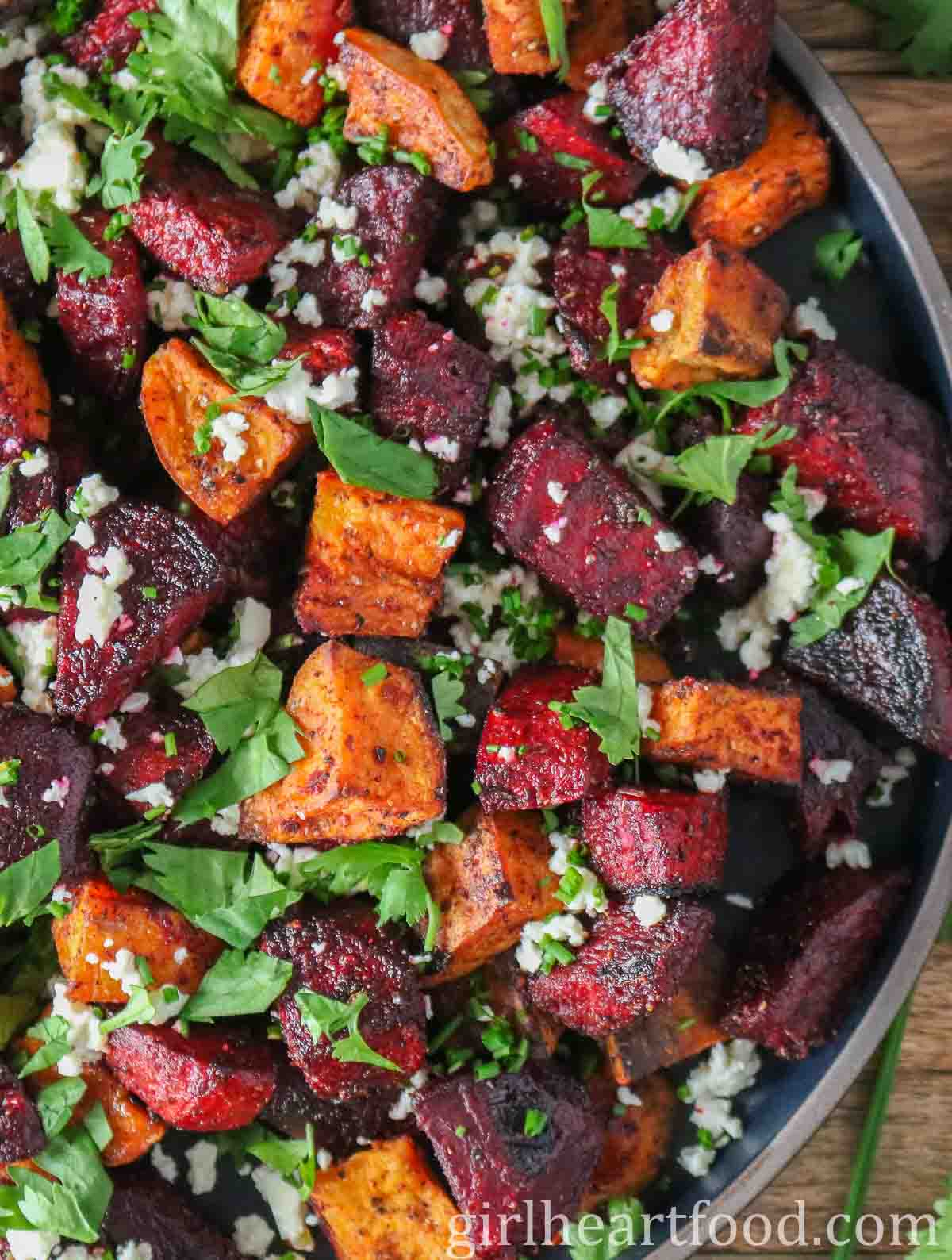 Close-up of a plate of roasted chunks of beet and sweet potato with feta & cilantro over top.