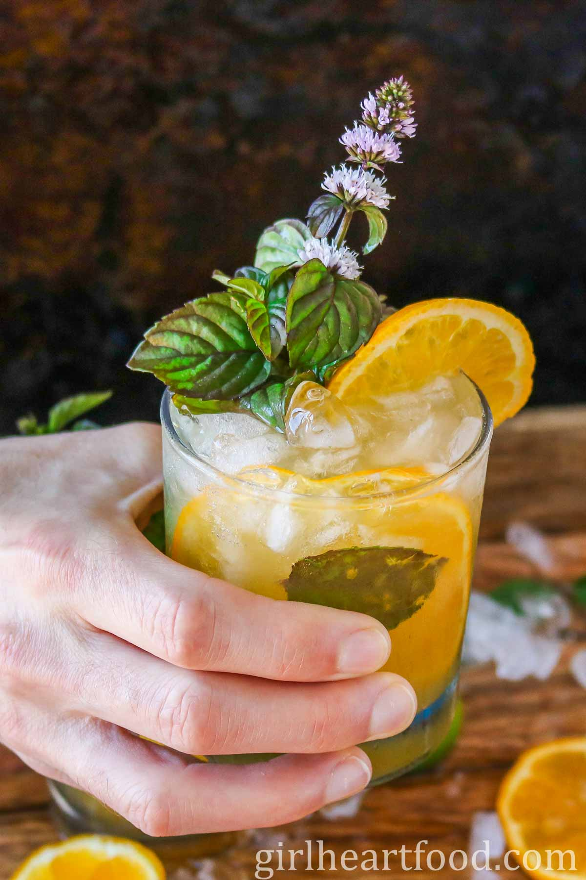 Hand holding a glass of orange mojito.