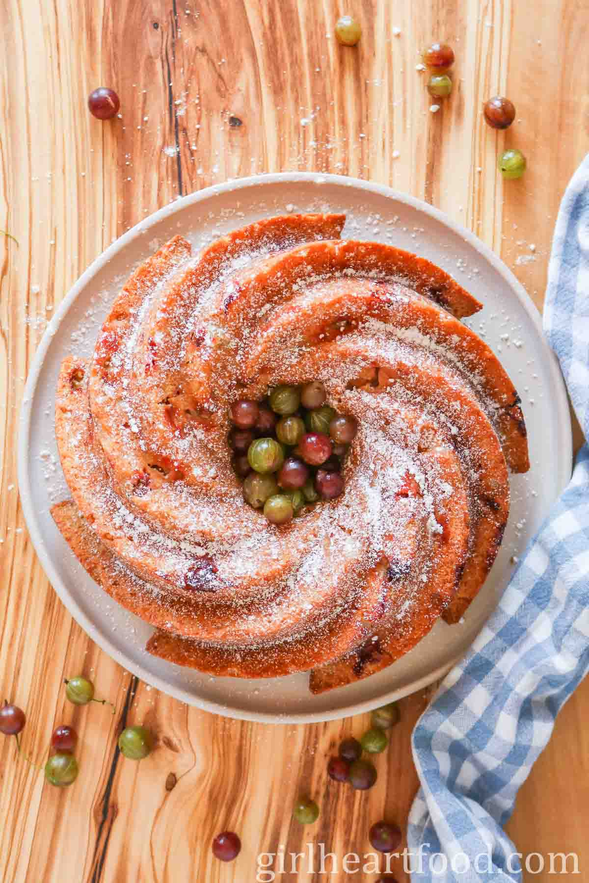 Overhead shot of a gooseberry bundt cake on a plate dusted with icing sugar and alongside some fresh gooseberries.