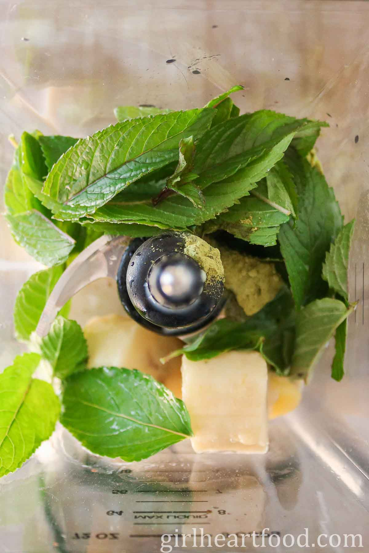 Ingredients for a mint and green tea matcha smoothie in a blender before being blended.