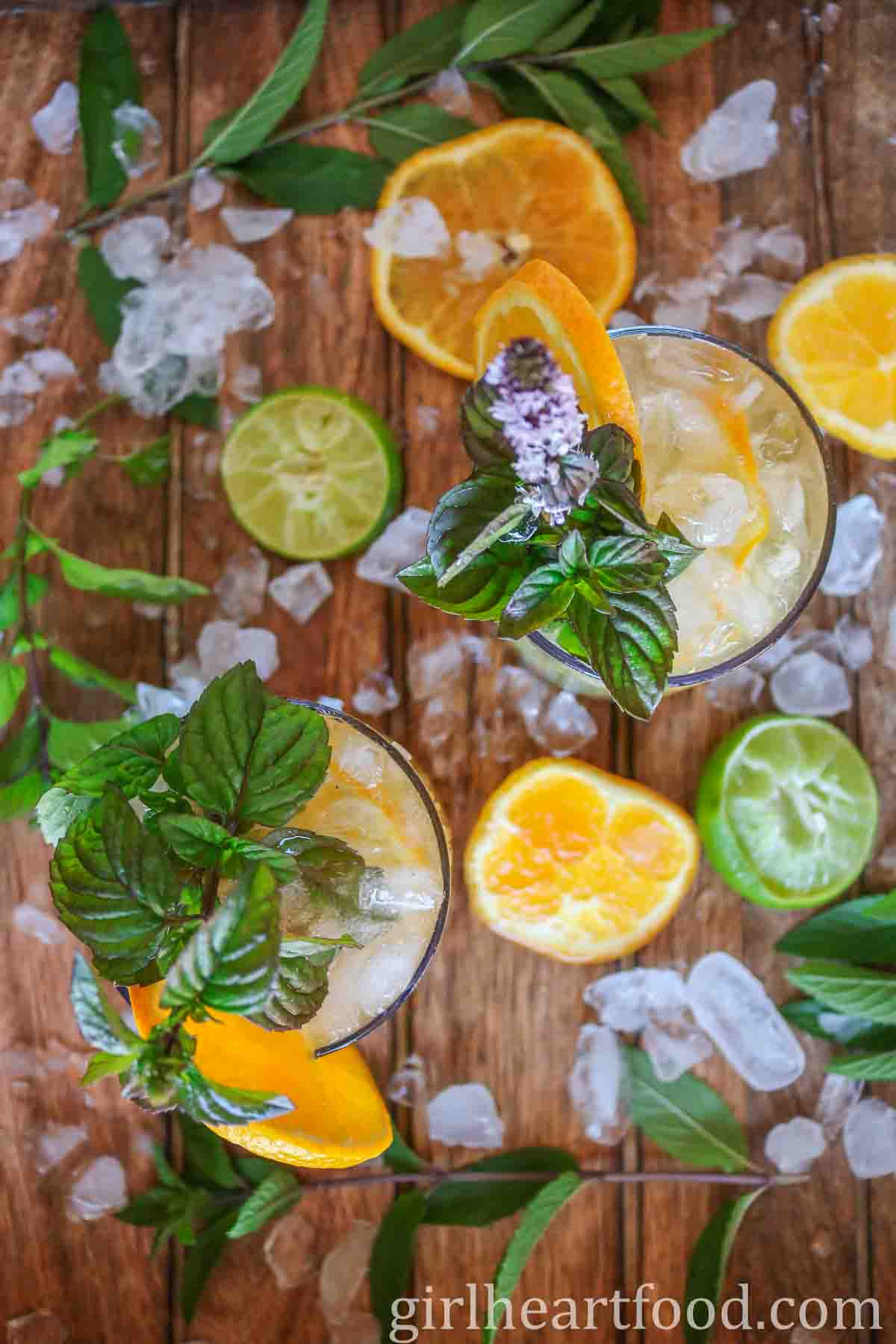 Two glasses of orange mojito garnished with mint and slice of orange.