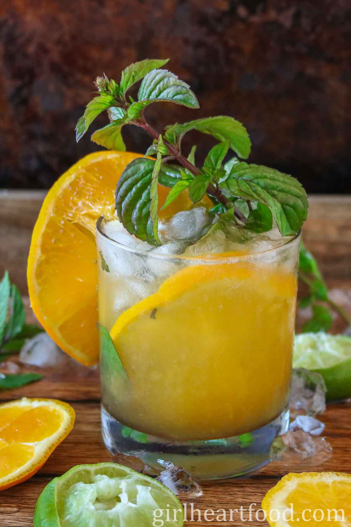Glass of orange cocktail garnished with fresh mint and an orange slice.