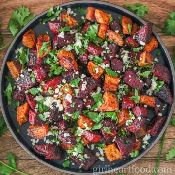 Large round plate with chunks of roasted beet and sweet potato with crumbled feta and cilantro on top.