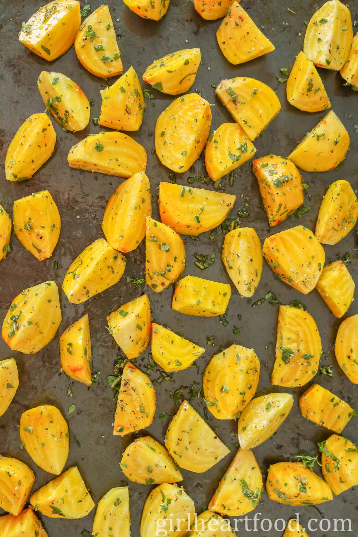 Chunks of golden beet with herbs on a sheet pan before being roasted.