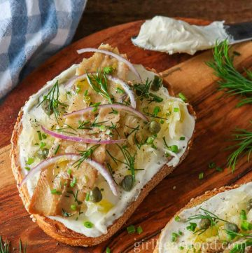 Portion of smoked herring fish with cream cheese on toast with sauerkraut, onion, capers and dill.