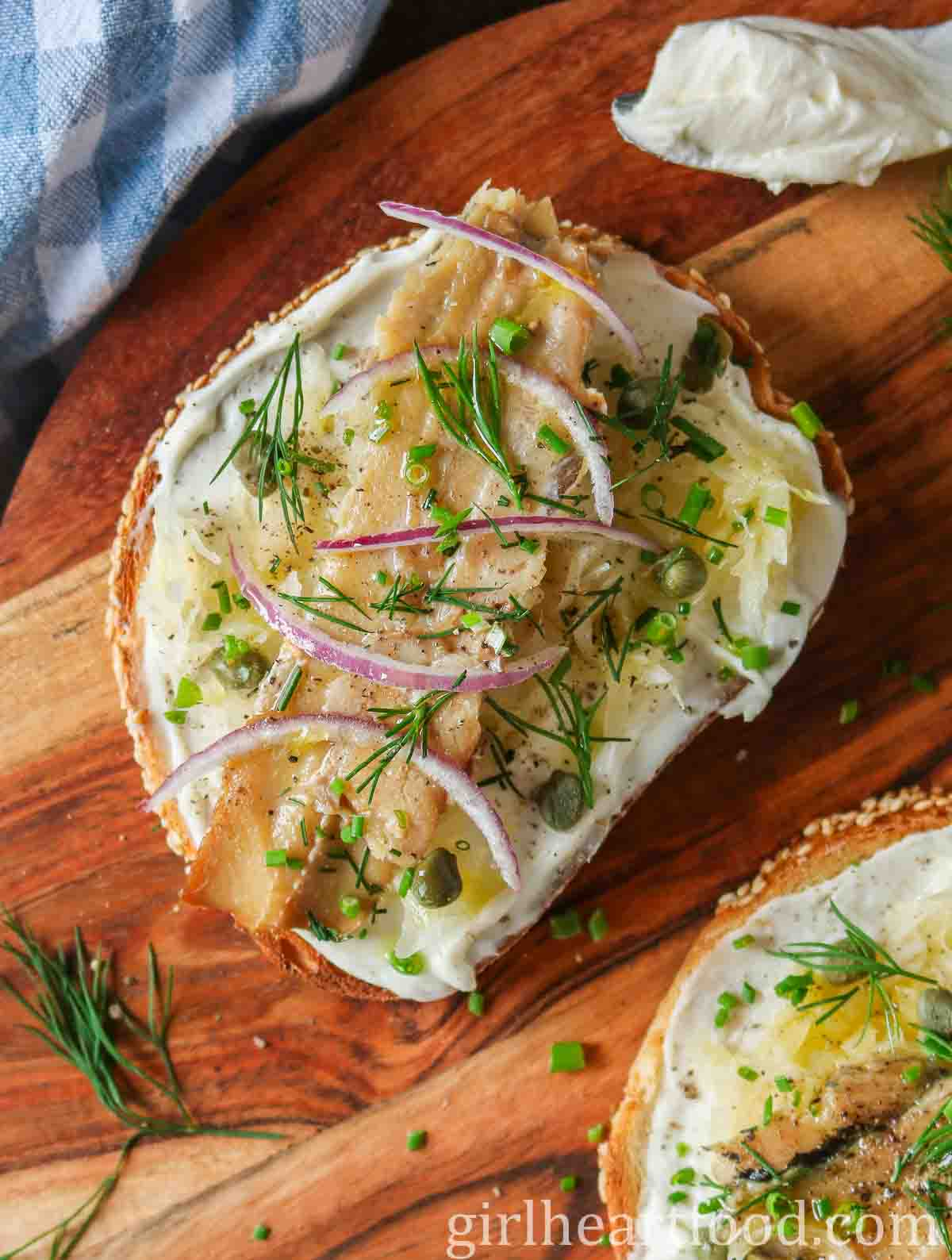 Overhead shot of an open face herring sandwich on a wooden board.