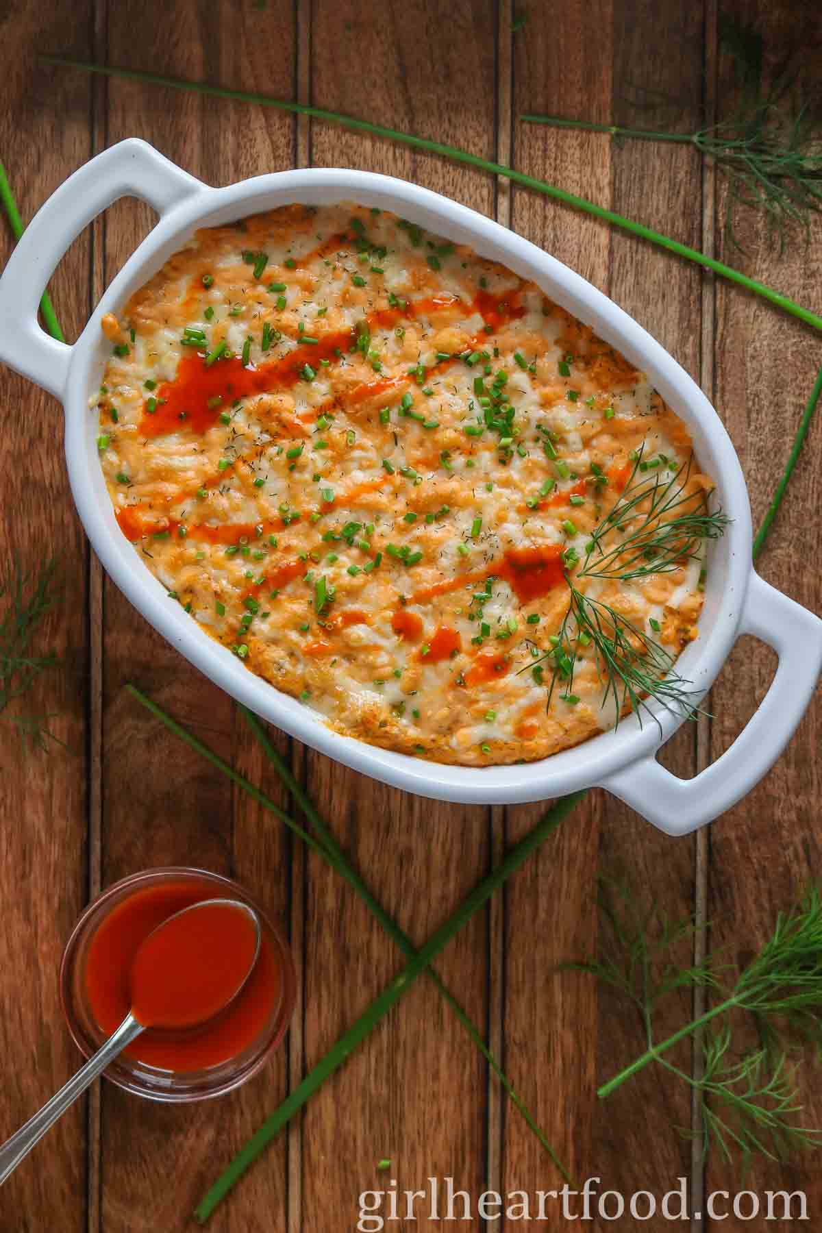White oval dish of cheesy buffalo dip alongside a dish of hot sauce with a spoon in it.