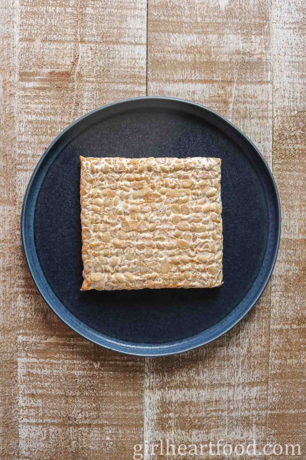 Block of uncooked tempeh on a dark blue plate.