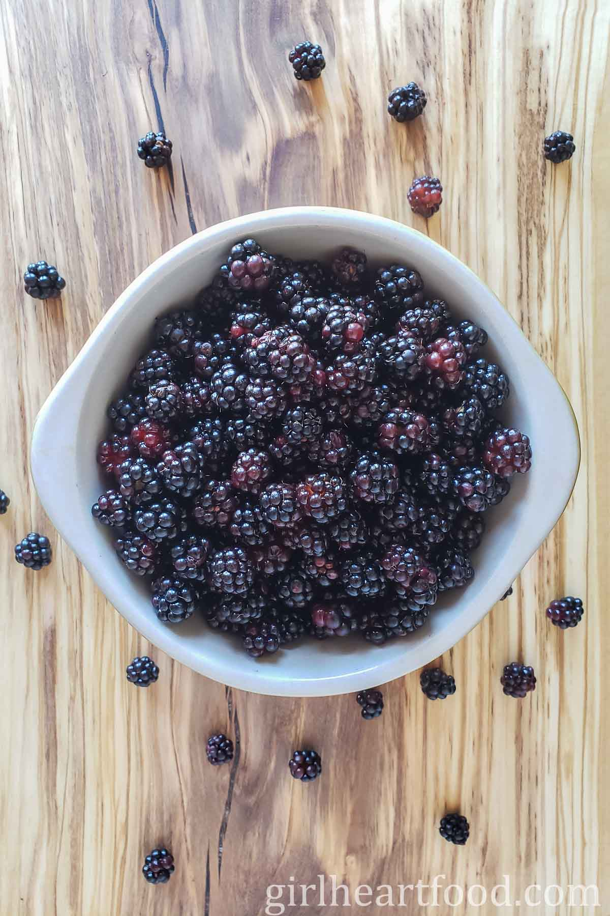 Bowl of fresh blackberries with some on a wooden board.