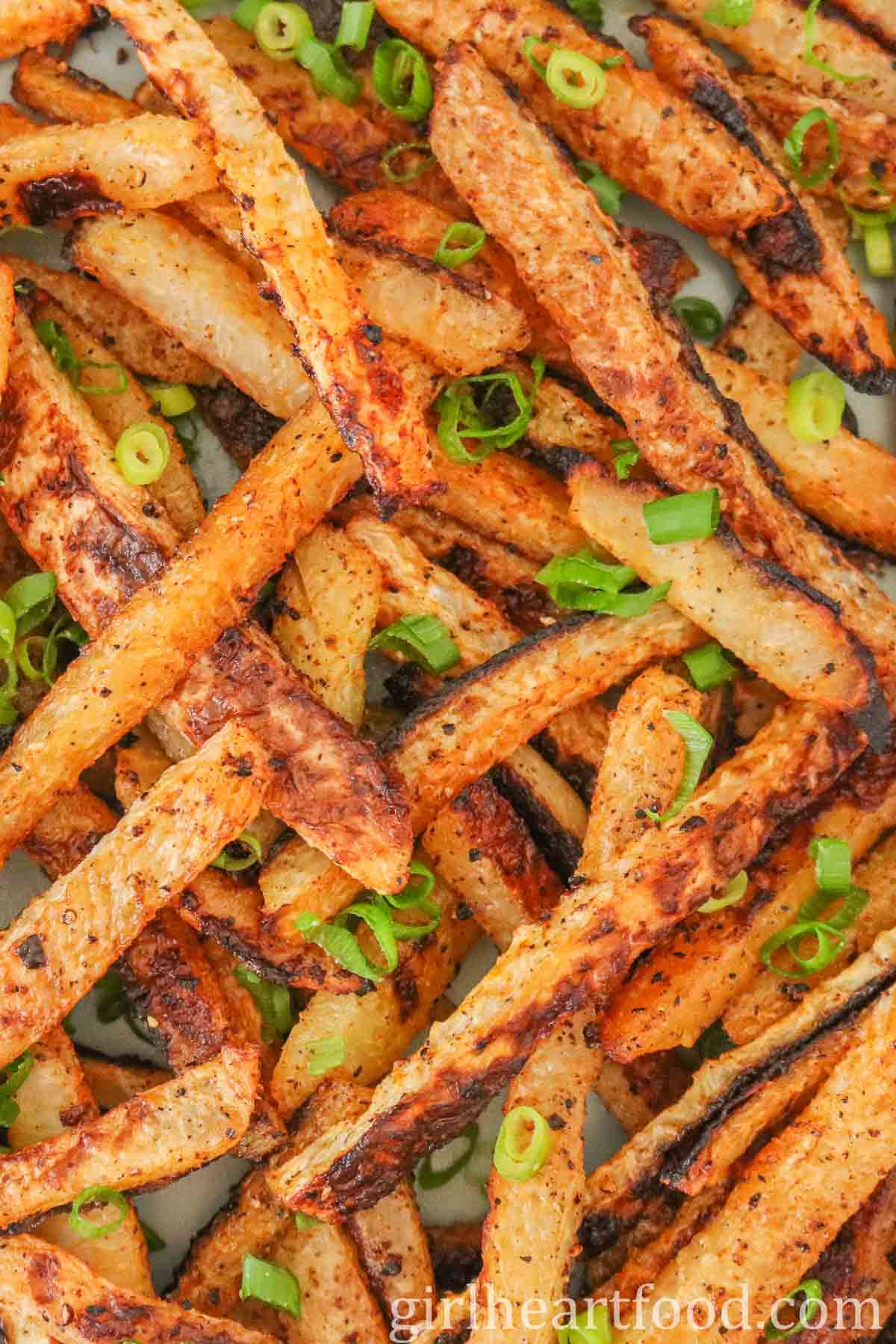 Tight close-up of baked kohlrabi fries garnished with green onion.