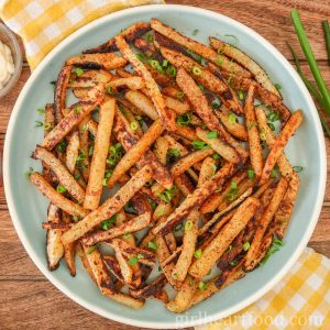 Plate of oven-baked kohlrabi fries garnished with green onion on a checkered tea towel.