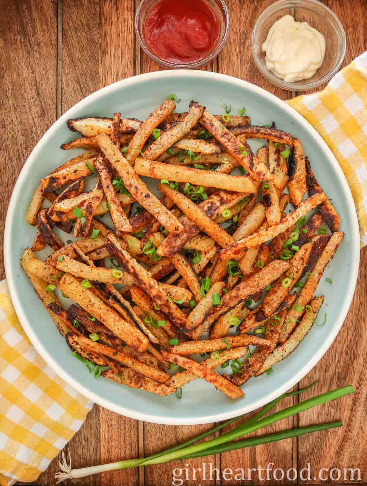 Blue plate of baked kohlrabi fries garnished with green onion and alongside dipping sauces.