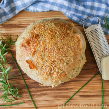 Overhead shot of a loaf of rosemary parmesan bread alongside some fresh herbs and a grater with block of parmesan cheese.