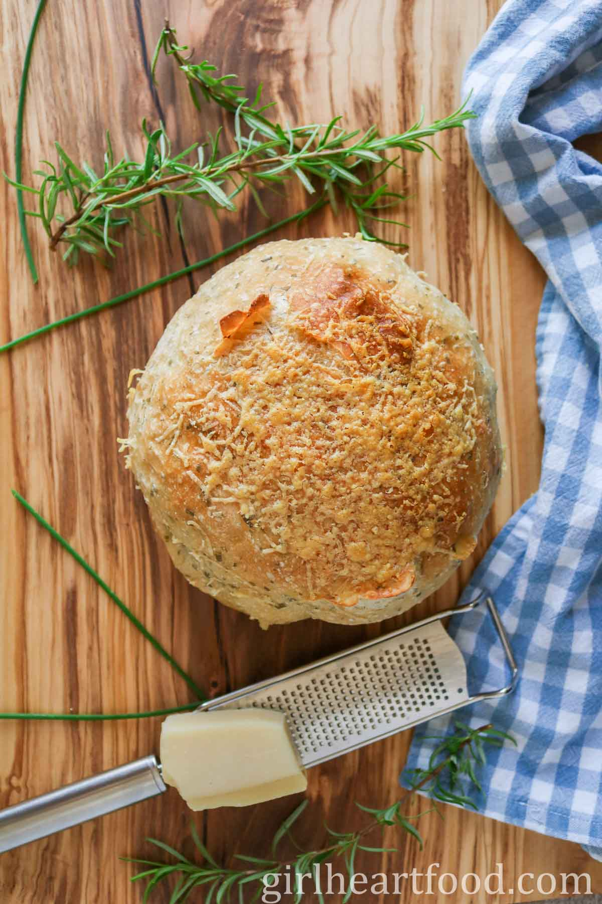 Round loaf of cheesy herb bread alongside fresh herbs, a grater and Parmesan cheese.