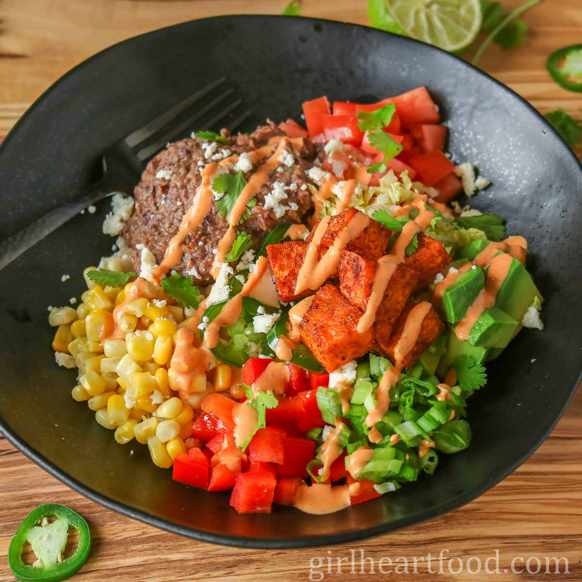 Refried Bean and vegetable burrito bowl drizzled with chipotle yogurt sauce.