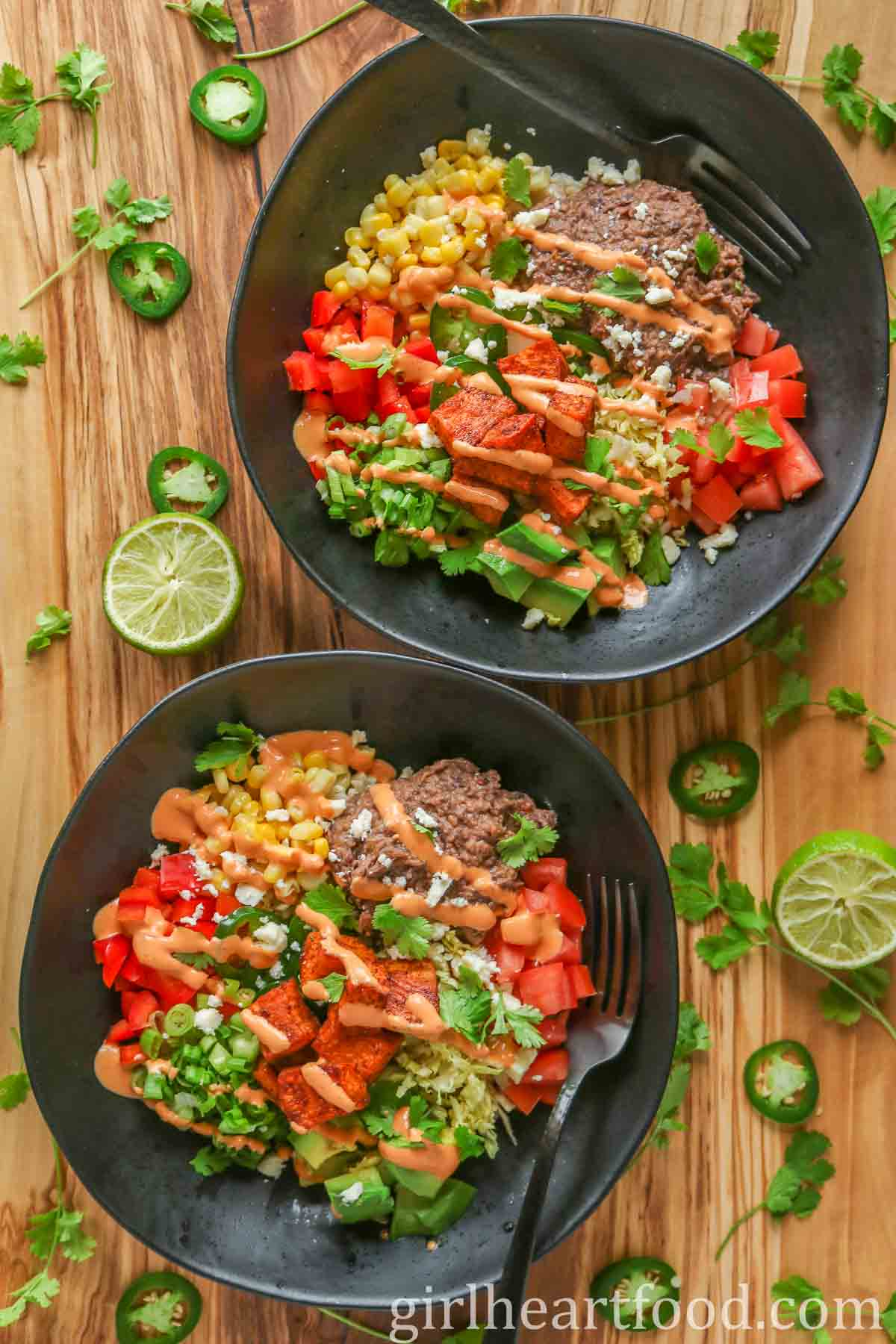 Two refried bean and veggie burrito bowls drizzled with chipotle sauce.