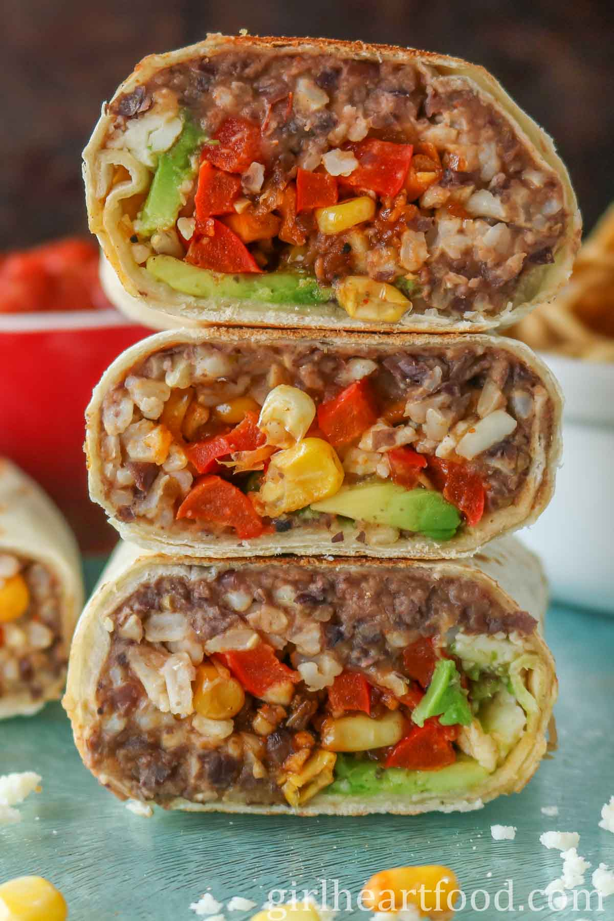 Three pieces of a refried bean burrito stacked on top of each other.