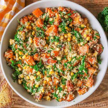 Large round dish of roasted squash, kale, corn and quinoa salad.