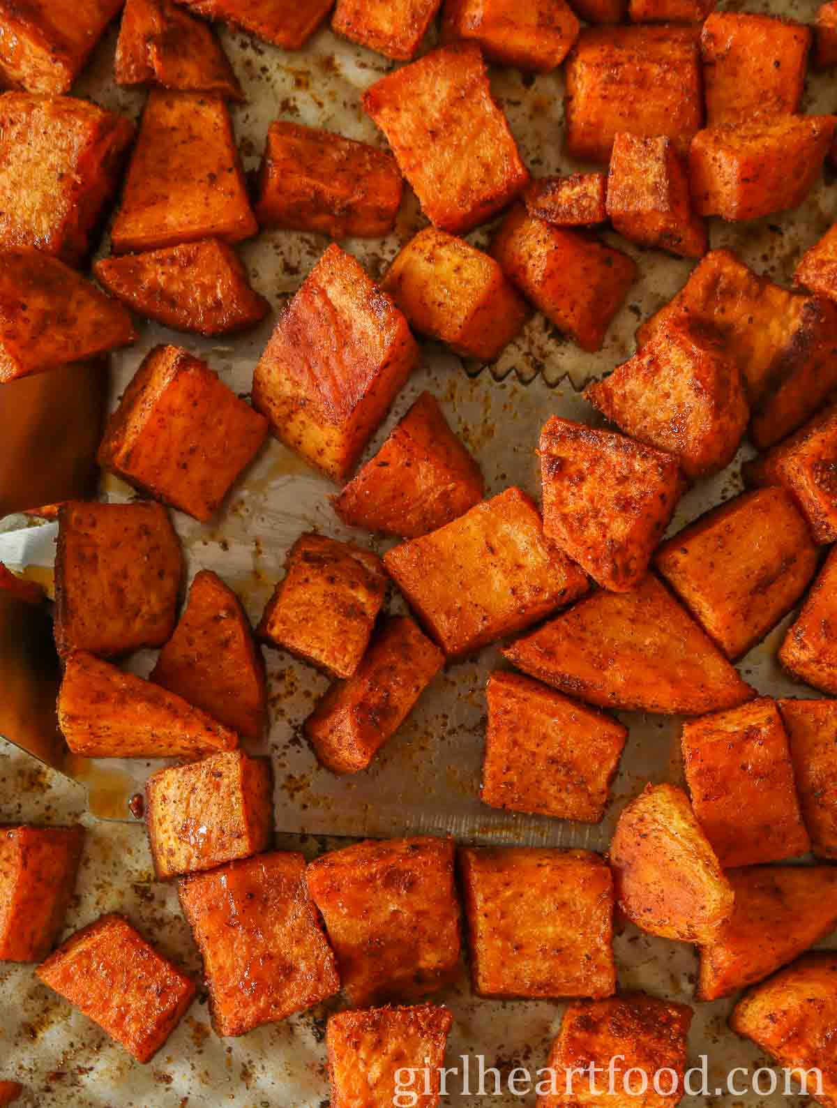 Cubes of roasted sweet potato on a sheet pan with a spatula underneath some.