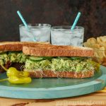 Tuna avocado salad sandwiches on a blue board next to hot peppers, glasses of water and potato chips.