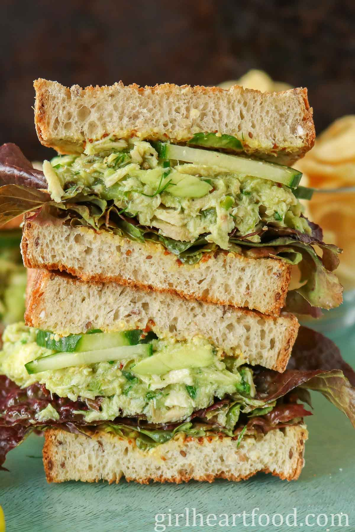 Two halves of a avocado tuna sandwich with lettuce and cucumber stacked on top of each other.