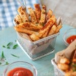 Small stainless steel basked of oven baked turnip fries garnished with parsley and alongside dish of ketchup.
