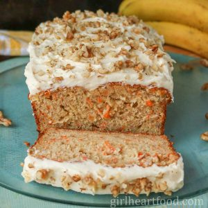 Cream cheese frosted loaf of carrot cake banana bread with a slice cut out of the loaf.