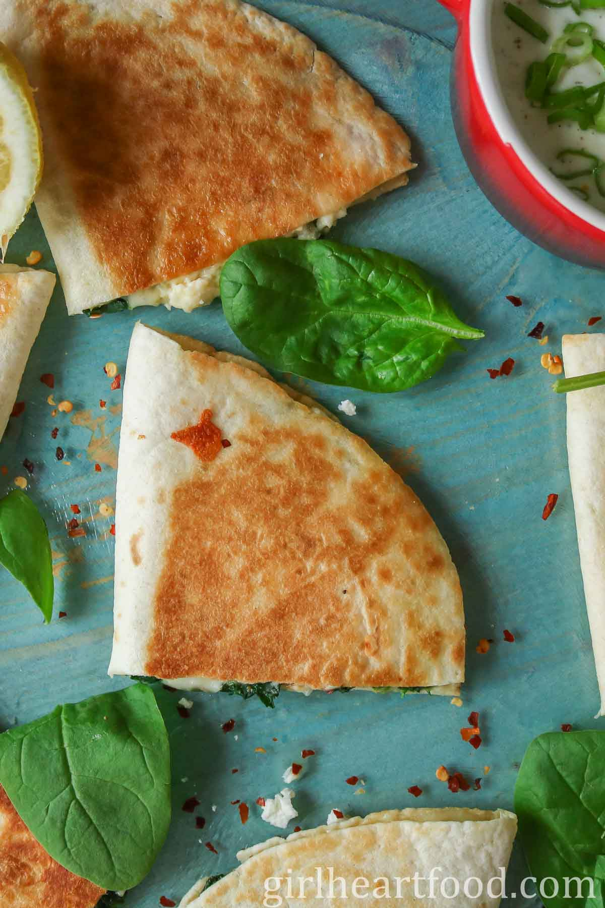 Overhead shot of crispy quesadillas on a blue board next to baby spinach, feta and chili flakes.