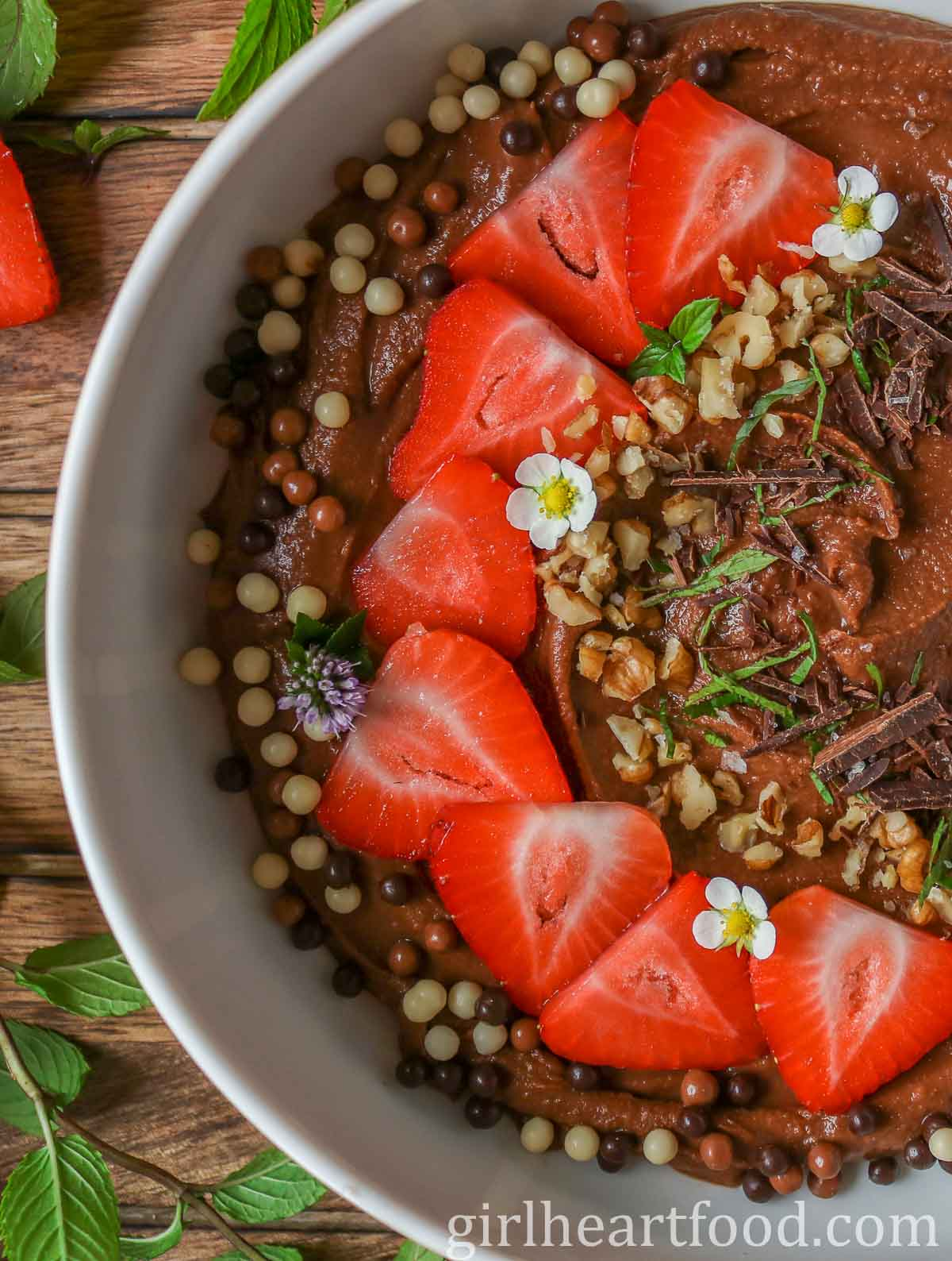 Close-up of a bowl of chocolate hummus garnished with toppings.