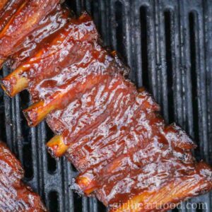 Overhead shot of a rack of BBQ sauce pork ribs on the grill.