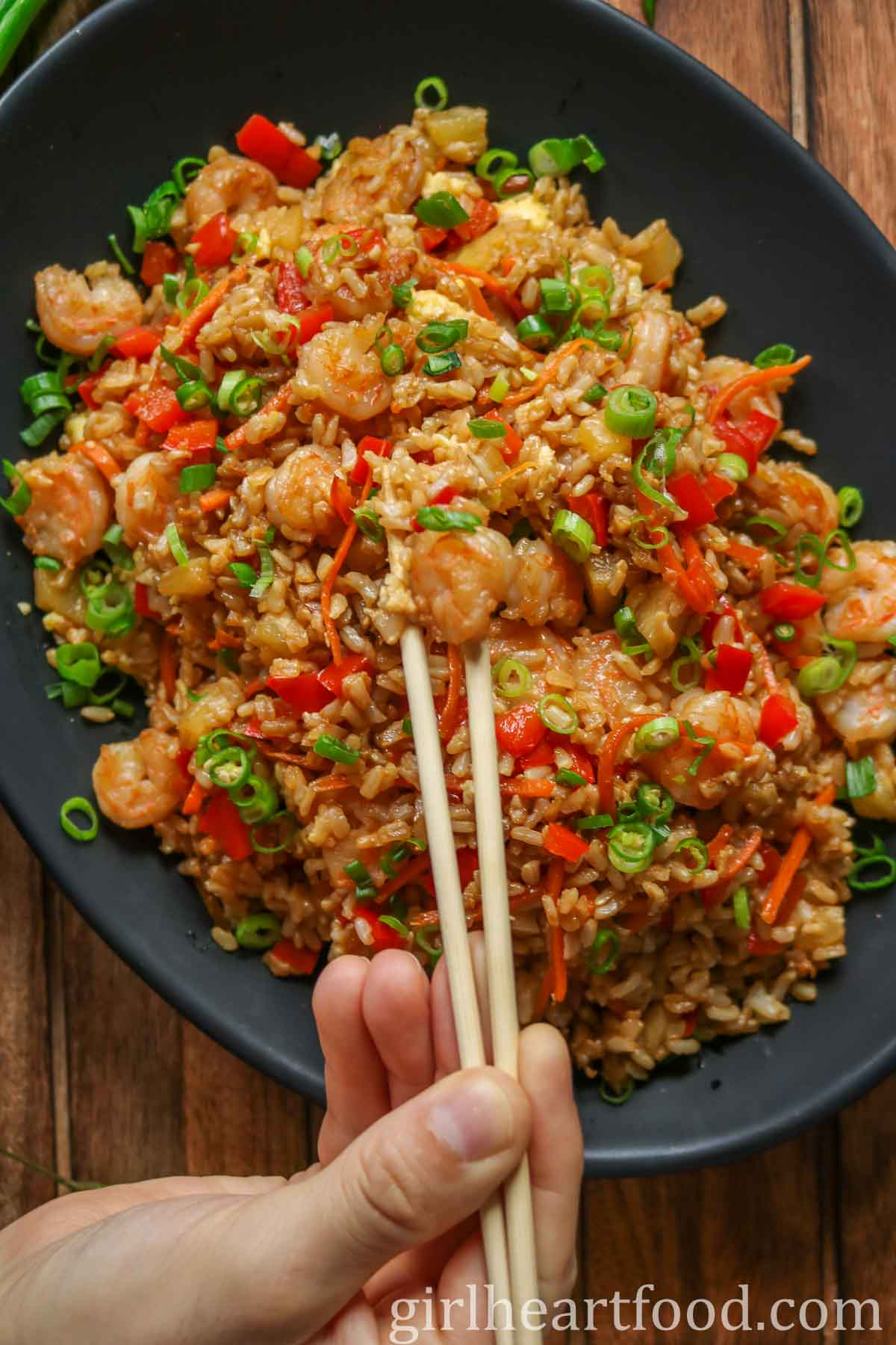 Hand holding chopsticks and scooping up some pineapple shrimp fried rice from a platter.