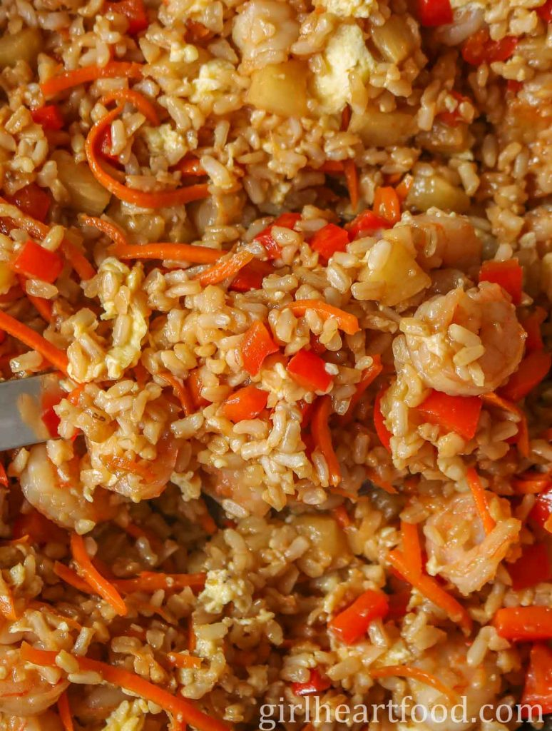 Close-up of fried rice with shrimp, pineapple and vegetables with a large serving spoon dunked into it.