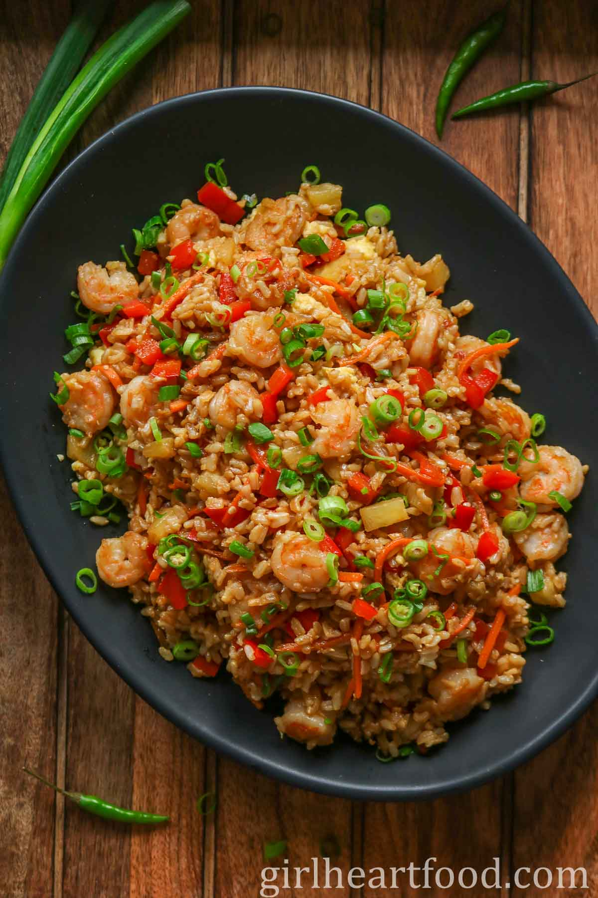 Pineapple shrimp fried rice on a black platter next to chili peppers and green onion.